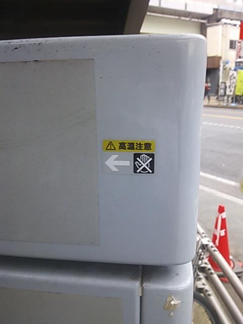 「高温注意」のステッカーの貼られた道ばたの謎の灰色の箱の写真