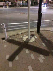 道路に落ちた十字架の形の影の写真